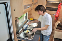 Family vacation, RV holiday trip, travel and camping, man cooking in camper interior Stock Images