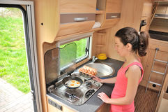 Family vacation, RV holiday trip, travel and camping, woman cooking in camper, motorhome interior. Family vacation, RV holiday trip, travel and camping, happy stock photo