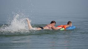 Family vacation at the sea. Boys on an air mattress, in flippers dressed on their hands, surf the sea. The woman