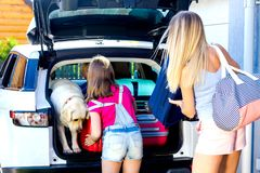Family vacation suitcases Labrador dog girl boy kid baggage blue pink orange house sun summer luggage car ready holidays green tra. Mother, girl and boy are Royalty Free Stock Image