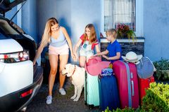 Family vacation suitcases Labrador dog girl boy kid baggage blue pink orange house sun summer luggage car ready holidays green tra. Mother, girl and boy are Royalty Free Stock Photos