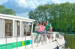 Family vacation, summer holiday travel on barge boat in canal, happy kids and parents having fun on river cruise trip in houseboat Stock Photo