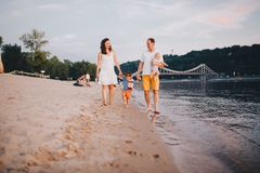 Family vacation in summer. Young Caucasian family foot walking barefoot sandy beach, shore river water. Dad mom holding hands two royalty free stock photos