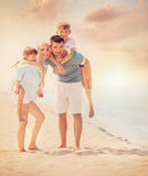 Family, vacation, tourism concept. Family of four having fun at the beach Stock Photography