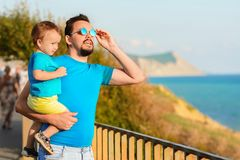 Family vacation and travel concept: father and little son are looking at something standing on embankment on a seashore. Mountains stock photos