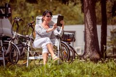 Family vacation travel, holiday trip in motorhome RV. Woman looking at the tablet near the camping . Caravan car Vacation. Family vacation travel, holiday trip royalty free stock image