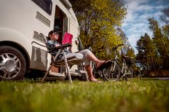 Family vacation travel, holiday trip in motorhome. Woman relaxes and reads a book near the camping . Caravan car Vacation. Family vacation travel, holiday trip royalty free stock photo