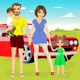 Family on vacation trip standing together near their red car Royalty Free Stock Photo