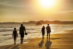 Family vacation in the tropics by the sea - silhouettes of people walking on the beach at sunset. stock photography