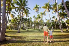 Family at vacation. Family of two, father and son, enjoying beautiful view at palm trees and tropical island at fiji, family vacation concept Stock Photo