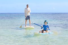 Family at vacation. Family of two, little boy and young father, enjoying stand up paddleboarding together at fiji, active family vacation concept Royalty Free Stock Photos