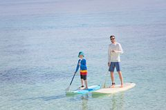 Family at vacation. Family of two, little boy and young father, enjoying stand up paddleboarding together at fiji, active family vacation concept Stock Photo