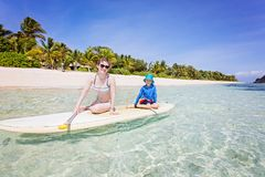 Family on vacation. Wide angle shot of family of two, mother and son, enjoying stand up paddleboarding in beautiful turquoise lagoon at fiji island, active Royalty Free Stock Photo