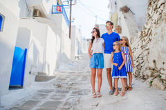 Family vacayion in Europe. Parents and kids at street of typical greek traditional village with white walls and colorful Stock Image