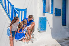 Family vacayion in Europe. Parents and kids at street of typical greek traditional village with white walls and colorful Stock Photo