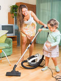 Family with vacuum cleaner Royalty Free Stock Photos