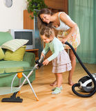 Family with vacuum cleaner Stock Photos