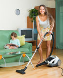 Family with vacuum cleaner Stock Image