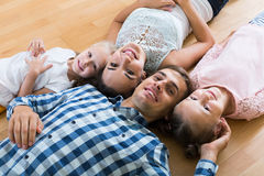 Family values: portrait of parents with little girls indoors Royalty Free Stock Photography