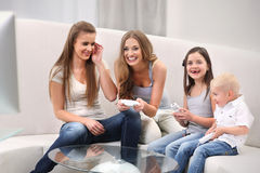 Family playing video game. Group of four people playing the game while sitting in the living room Royalty Free Stock Images