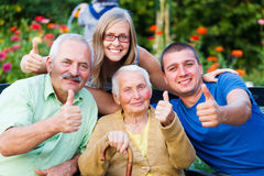 Family Visit in the Nursing Home. Happy, contented family showing thumbsup for the quality of the residential care of grandmother Stock Images