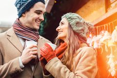 Couple standing on Christmas market in front of gift stall royalty free stock photography