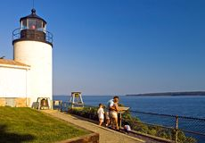 Family visiting lighthouse. A view of a family on vacation, sightseeing at the Bass Harbor Lighthouse, Maine, stopping to take in the scenery along the beautiful Stock Photography