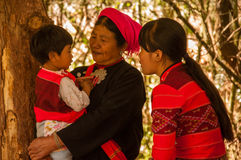 A family of Wa Group in traditional clothes. This is shot in a village called Weng'ding, located in southwest of Yunnan province. It's a Wa village. The mother Royalty Free Stock Photography