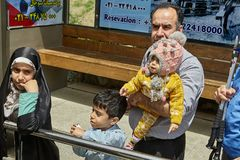 Family are waiting for public transport at bus stop, Iran. Tehran, Iran - April 28, 2017: An Iranian family, a father with threefamily, is waiting for the bus stock photography