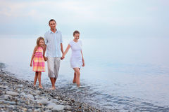 Family walk on beach in evening, focus on mother. Happy family with little girl walk on beach in evening, focus on mother Royalty Free Stock Photography