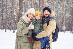 Family walk of Caucasian couple smiling and holding son on hands Stock Image