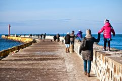 Family walk on Darlowo pier. Family of mother and daughter having a walk on Darlowo harbour pier (Poland, Baltic). Sunny winter day royalty free stock photography