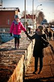 Family walk on Darlowo pier. Family of mother and daughter having a walk on Darlowo harbour pier (Poland, Baltic). Sunny winter day stock photo