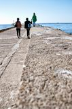 Family walk on Darlowo pier. Family of three women walking on Darlowo (Poland) pier towards harbour entrance beacons on a spring day royalty free stock photos