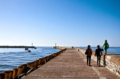 Family walk on Darlowo pier. Family of three women walking on Darlowo (Poland) pier towards harbour entrance beacons on a spring day Royalty Free Stock Image
