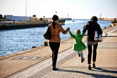 Family walk on Darlowo pier. Family of three women walking on Darlowo (Poland) pier towards harbour entrance beacons on a spring day stock image