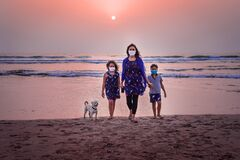 Family walk on the ocean at sunset.
