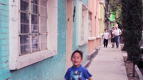 A family walk over the sidewalk after school, a boy runs. MEXICO CITY, 2016 (ILLUSTRATIVE IMAGE). A family walk over the sidewalk after school, a boy runs stock footage