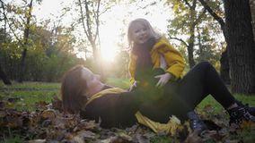 Family walk, portrait of little charmingly cute girl with her attractive young mother who have fun in autumn park