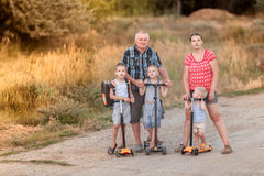 Family walk on scooters with his wife and children on the village road. Near Volgograd area stock image