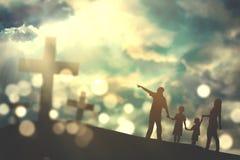 Family walk towards crucifix symbols. Silhouette of family walking on the hill towards three crucifix symbols with bright sunlight on the sky stock image