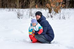 Family walk in winter forest dad mom and child royalty free stock photo
