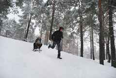 Family on a walk in a winter snow-covered forest. Stock Photo