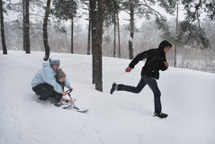 Family on a walk in a winter snow-covered forest. Royalty Free Stock Photos