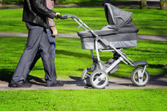 Family walking. Couple with the man pushing a baby carriage, walking through a park royalty free stock photography