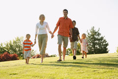 Family Walking. Young Caucasian family walking on a grassy hill holding hands and smiling Stock Photos