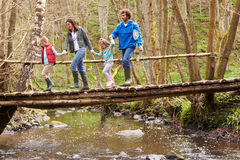 Family Walking Across Wooden Bridge Over Stream In Forest Stock Image