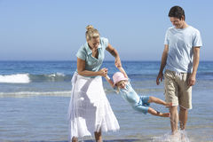 Family walking along beach, ankle deep in water, mother swinging daughter (2-4), smiling Stock Photo