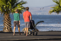Family walking along the beach front. Royalty Free Stock Photo