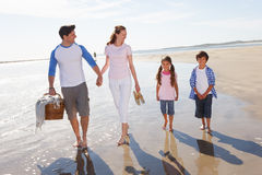 Family Walking Along Beach With Picnic Basket Stock Photos